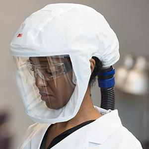 Healthcare professional wearing a powered air purifying respirator PAPR with hood and tubing visible
