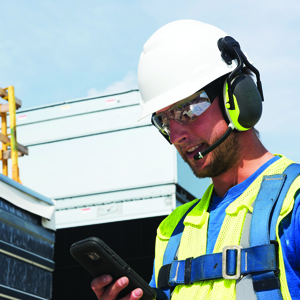 construction worker setting up wireless communication hearing protection